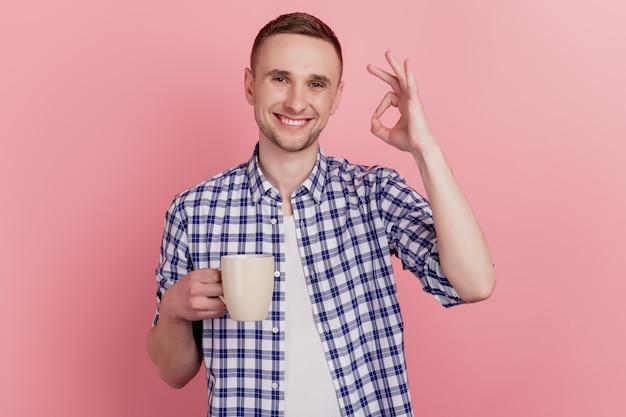 Photo gros plan de beau jeune homme heureux sourire positif tenir tasse café show ok signe boire fond pastel isolé