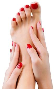 Photo en gros plan d'un beau pied féminin avec pédicure et mains avec manucure