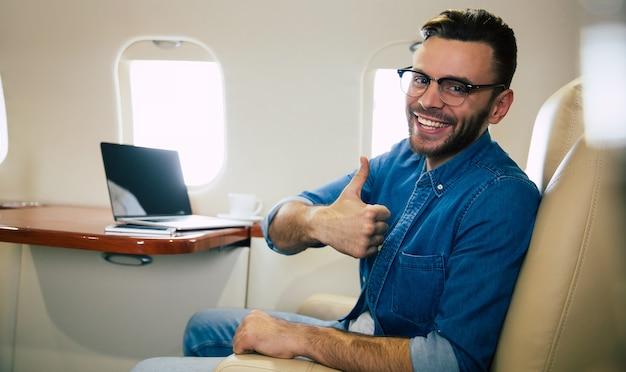 Photo en gros plan d'un bel homme dans une tenue décontractée, qui sourit, tout en tapant quelque chose sur son ordinateur portable et tenant un smartphone dans sa main gauche, volant en première classe d'avion.