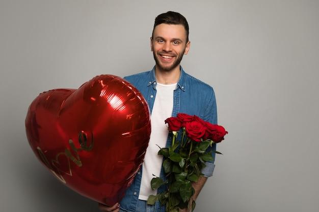 Photo en gros plan d'un bel homme, qui regarde dans l'appareil photo, tenant un gros ballon rouge en forme de coeur et un bouquet de roses et souriant.