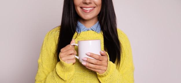 Photo en gros plan de la belle brune, qui pose dans un pull jaune, regardant de côté et souriant tout en tenant une tasse de thé blanc