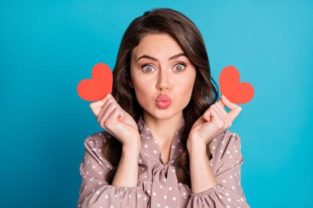 Photo en gros plan de la belle charmante dame drôle tenir deux petites cartes de coeur rouge humeur romantique envoyant des baisers aériens petit ami porter une robe en pointillés fond de couleur bleu isolé