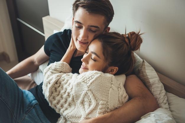 La photo en gros plan d'une belle femme embrassant son amant au lit portant des vêtements chauds tôt le matin