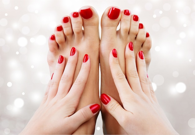 Photo en gros plan d'une belle femme pieds avec pédicure et mains avec manucure