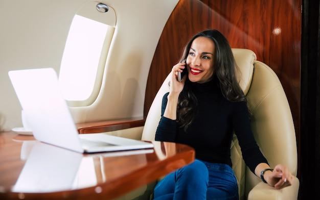 Photo en gros plan d'une belle femme en tenue décontractée, qui parle au téléphone et boit du café noir pendant son vol en jet privé.