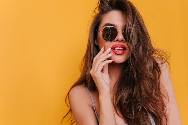 Photo en gros plan de la belle fille blanche à lunettes de soleil noires