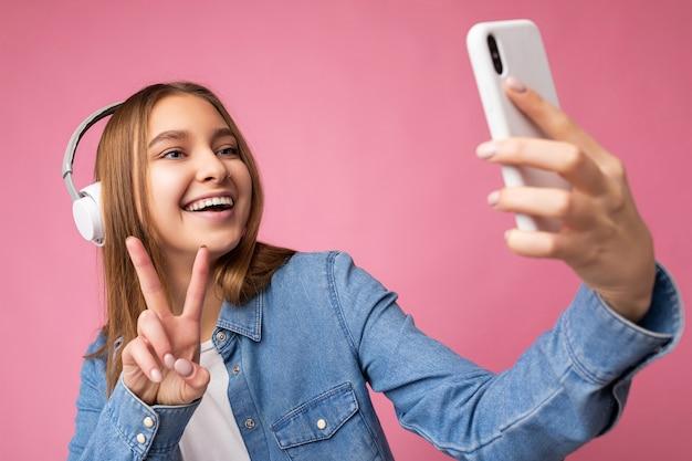 Photo gros plan d'une belle jeune femme blonde foncée souriante et positive portant une chemise élégante en jean bleu