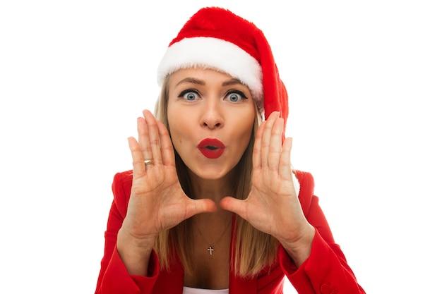 Photo en gros plan d'une belle jeune femme en bonnet de noel, tenant les mains autour de la bouche et faisant des grimaces