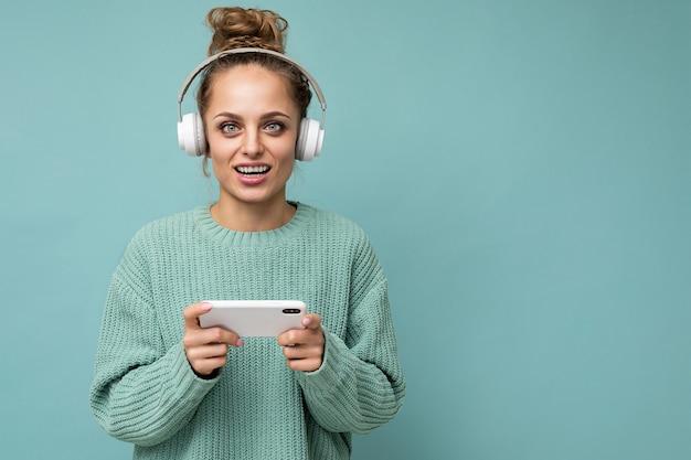 Photo gros plan d'une belle jeune femme heureuse et positive portant un pull bleu isolé sur bleu