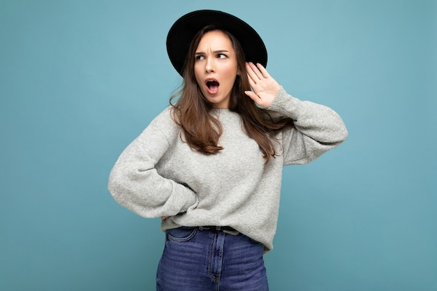 Photo en gros plan d'une belle jeune femme surprise choquée et étonnée avec la bouche ouverte portant