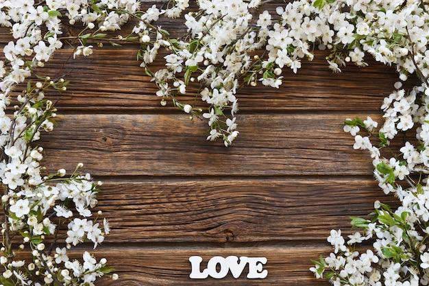 Photo en gros plan de belles branches blanches de cerisier en fleurs avec des lettres blanches d'amour.