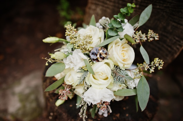 Photo en gros plan d'un bouquet de mariée composé de roses blanches et d'autres herbes, portant sur une surface en bois.