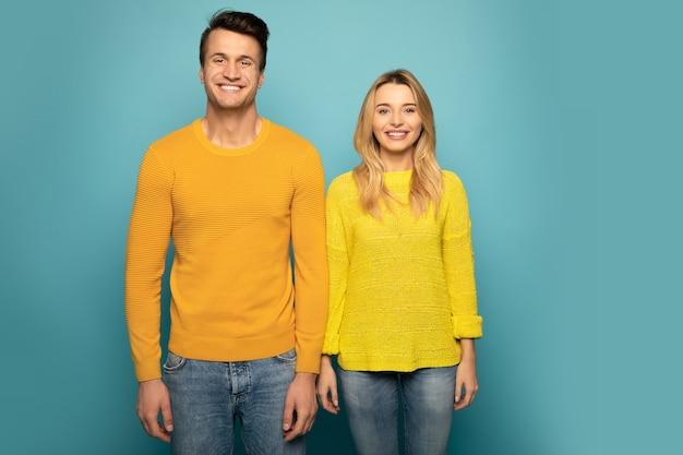 Photo en gros plan d'un charmant couple, qui pose dans des chandails jaunes, à la fois regardant dans l'appareil photo et souriant.