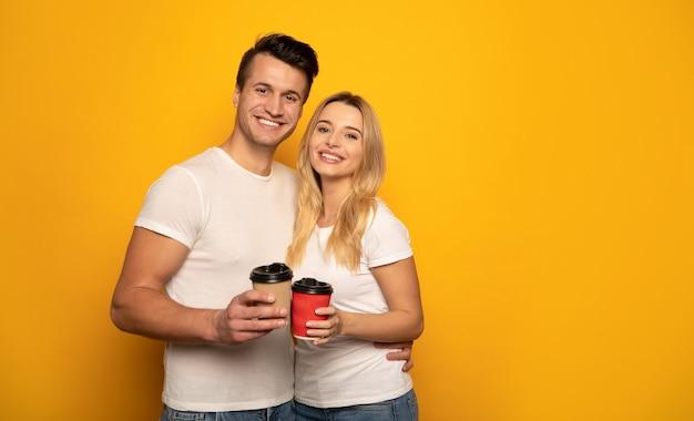 Photo En Gros Plan D'un Charmant Couple En T-shirts Blancs, Qui Tiennent Leurs Tasses à Café, Se Tiennent L'un Près De L'autre Et Ont L'air Heureux Devant L'appareil Photo. Photo Premium