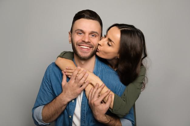Ð¡photo en gros plan d'une charmante dame aux cheveux châtains, qui embrasse son beau petit ami sur la joue, tout en le serrant dans le dos.