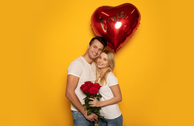 Ð¡photo en gros plan d'une charmante dame et de son beau petit ami, qui l'embrasse sur la joue, tout en lui offrant un bouquet de roses et un gros ballon rouge en forme de cœur.