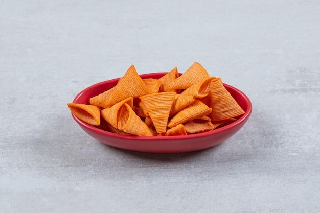 La photo en gros plan de chips épicées dans un bol rouge.