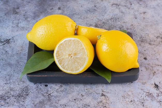 La photo en gros plan de citrons coupés entiers ou à moitié sur une plaque en bois.