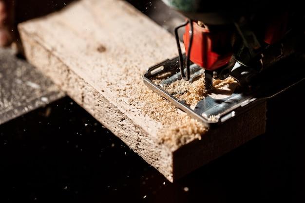 La photo en gros plan de couper du bois avec une scie à chantourner.