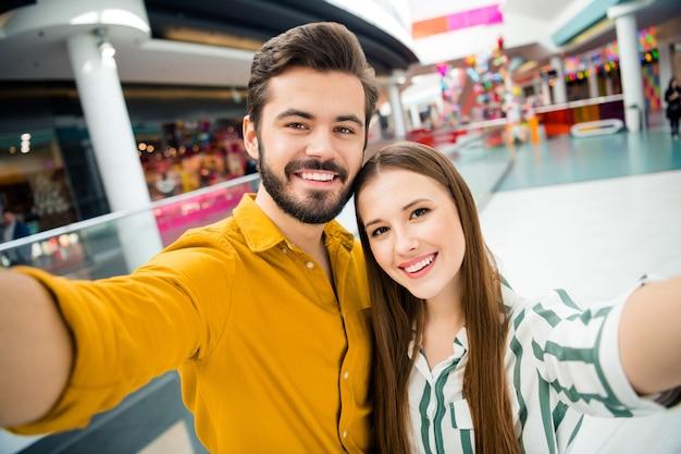 Photo en gros plan d'un couple de beau mec séduisant et drôle visiter le centre commercial du centre commercial ensemble en prenant des selfies de bonne humeur accros du shopping portent une tenue de chemise décontractée à l'intérieur