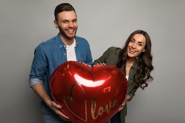 Photo en gros plan d'un couple joyeux dans des tenues décontractées, qui tiennent ensemble un gros ballon en forme de cœur, souriant et regardant dans la caméra