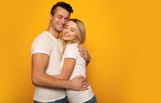 Photo en gros plan d'un couple mignon, étreignant étroitement et souriant tout en posant sur un fond jaune