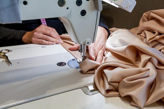Photo en gros plan de la couture du tissu au chocolat. la femme coud le tissu par une machine à coudre
