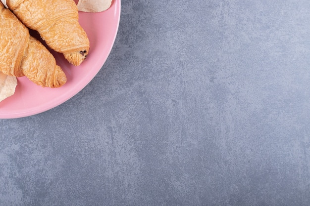 La photo en gros plan de croissant français sur plaque rose.
