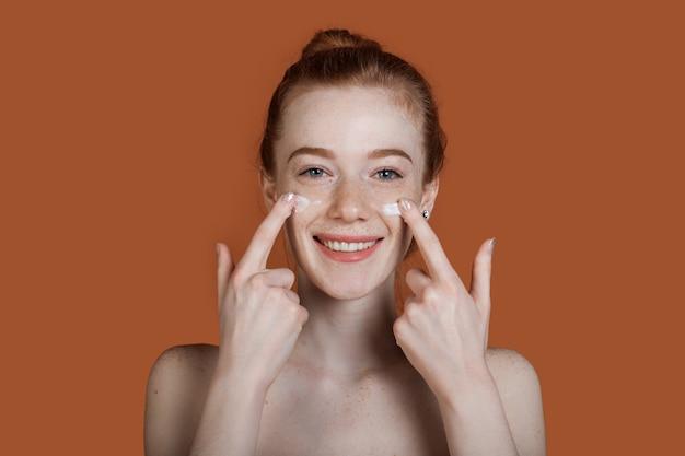 La photo en gros plan d'une dame au gingembre avec des taches de rousseur appliquant de la crème sur son visage posant
