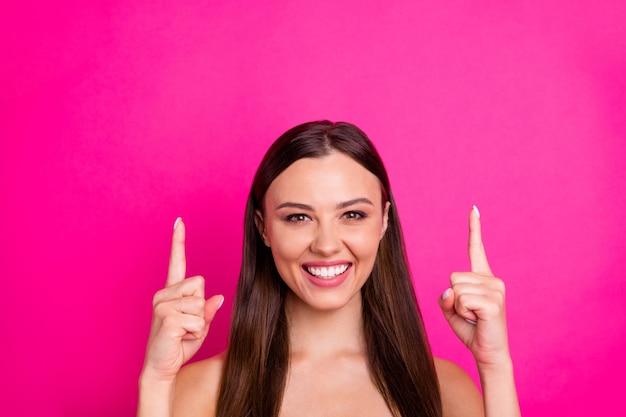 Photo gros plan d'une dame incroyable indiquant les doigts vers le haut de l'espace vide montrant des épaules nues nouveauté bas prix isolé fond de couleur rose vif