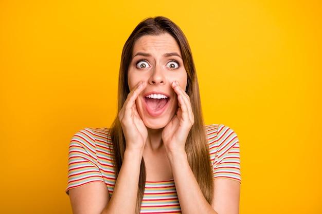Photo gros plan de dame terrifiée tenant la main près de la bouche crier fort voir rue voulait bandit porter un t-shirt rayé décontracté mur de couleur jaune isolé