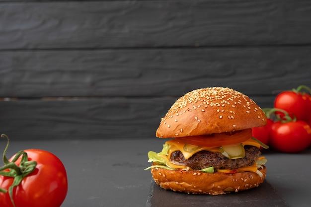 La photo en gros plan de délicieux burger frais sur fond noir