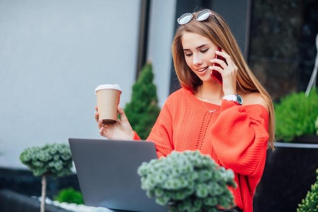 Photo en gros plan, deux femmes partenaires d'affaires tout en lisant un journal ensemble dans une cafétéria en plein air. écrire quelque chose.