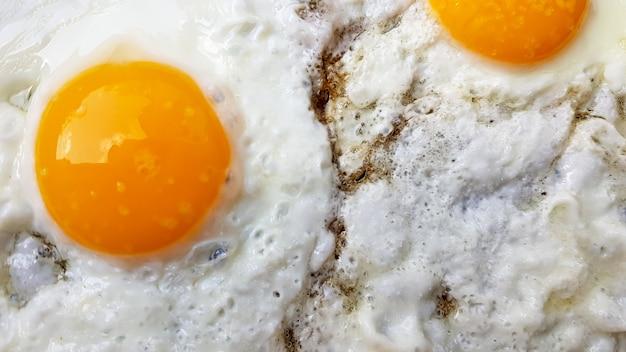 Photo en gros plan de deux œufs brouillés dans une poêle à frire noire.