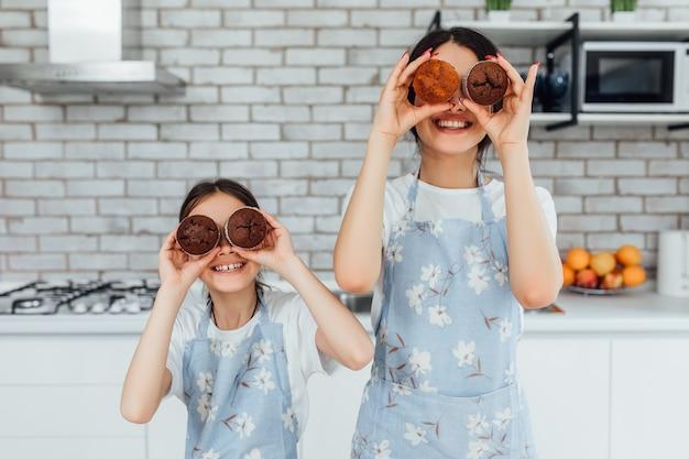 La photo en gros plan de deux sœurs jouant avec des cupcakes