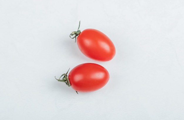 La photo en gros plan de deux tomates cerises. sur fond blanc. photo de haute qualité
