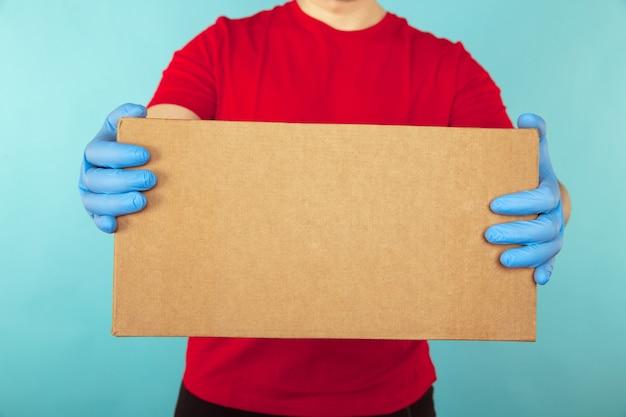 Photo gros plan du livreur dans des gants bleus tenant une boîte en carton.