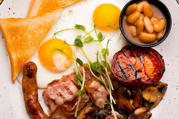 La photo en gros plan du matin savoureux petit-déjeuner anglais au restaurant sur table en bois