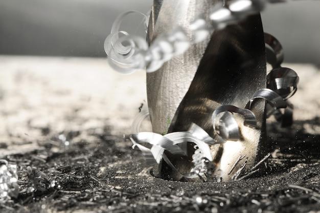 Photo gros plan du processus de forage de trous, copeaux de métal autour de la perceuse.