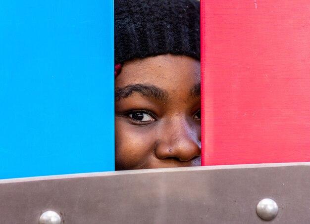 La photo en gros plan du visage d'une fille noire avec des tresses colorées. vêtu d'un pull rouge et d'un bonnet de laine noir.