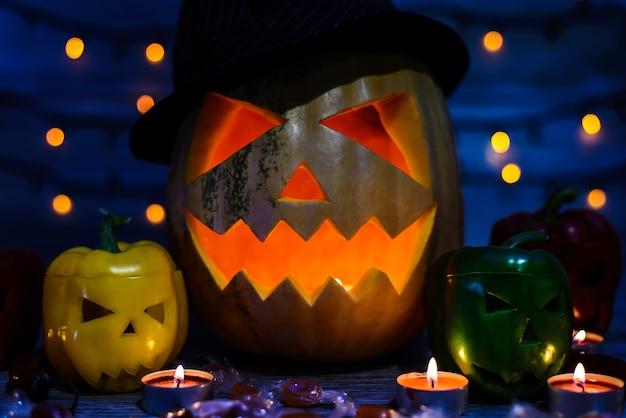 La photo en gros plan du visage spoofy de jack-o-lantern, poivrons avec des visages effrayants, chandelles, effet bokeh, bonbons