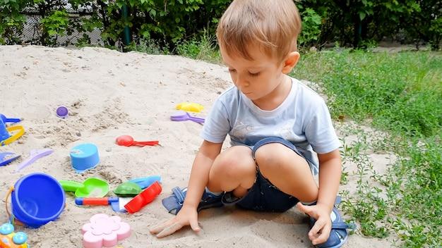 Photo gros plan d'un enfant de 3 ans jouant avec un jouet dans un bac à sable sur une aire de jeux
