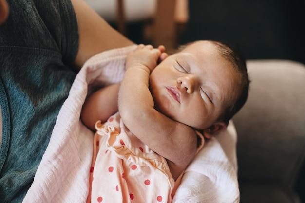 La photo en gros plan d'un enfant de race blanche faisant la sieste pendant que sa mère le tient