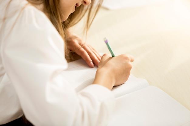 Photo gros plan sur l'épaule d'une fille qui écrit dans un cahier avec un crayon
