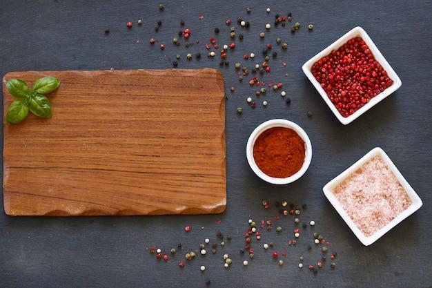 Photo en gros plan d'épices séchées colorées dans des bols blancs avec une planche de bois sur une table bétonnée noire