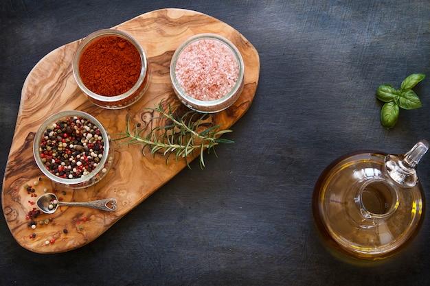 Photo en gros plan d'épices séchées colorées dans des bols sur une planche en bois sur une table bétonnée noire avec de l'huile d'olive dans un bocal