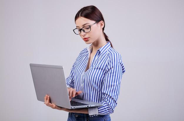 La photo en gros plan d'une femme administratrice dans une chemise rayée blanc-bleu avec des lunettes et un ordinateur portable sur fond gris. employé de l'année, femme d'affaires.