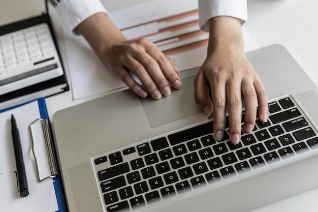 Photo en gros plan d'une femme en costume en train de taper sur un clavier d'ordinateur portable, d'une femme d'affaires tapant en train de discuter avec un partenaire commercial via une messagerie en ligne. concept d'utilisation de la technologie dans la communication.