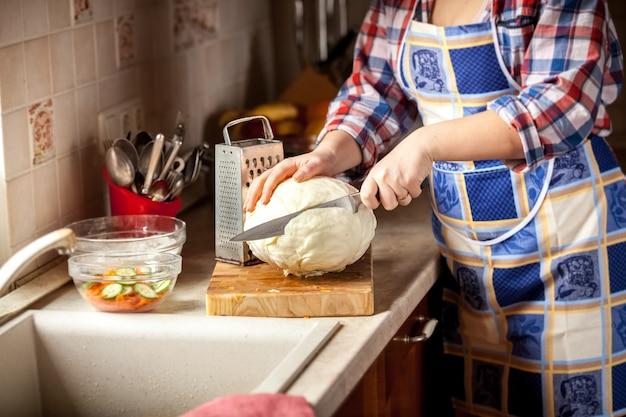 Photo gros plan d'une femme coupant le chou dans la cuisine