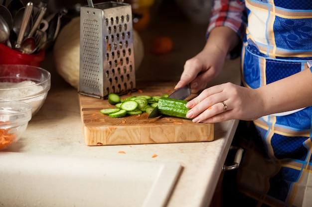 Photo gros plan d'une femme coupant le concombre sur une planche de bois